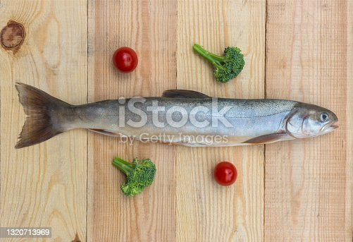 istock Raw rainbow trout river fish on a wooden background with vegetables 1320713969