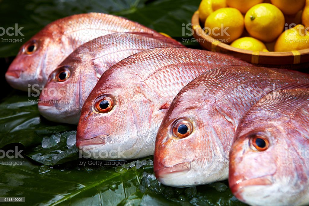 Raw Red Mullet Fishs on Green Banana Leaves with Lemons stock photo
