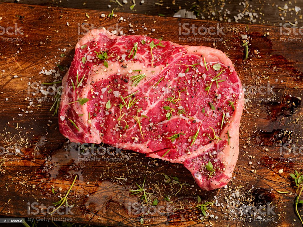 Raw Rib Eye Steak with Fresh Herbs stock photo