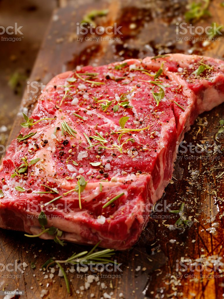 Raw Rib Eye Steak with Fresh Herbs stock photo