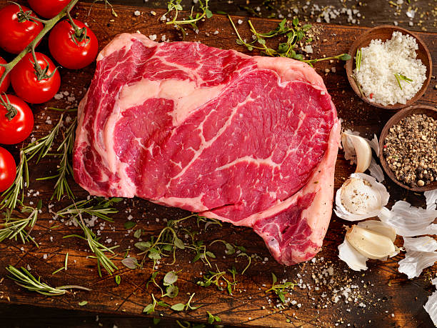 raw rib eye steak with fresh herbs - ribeye biefstuk stockfoto's en -beelden