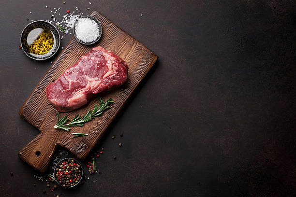 Raw ribeye beef steak cooking with ingredients - foto de acervo