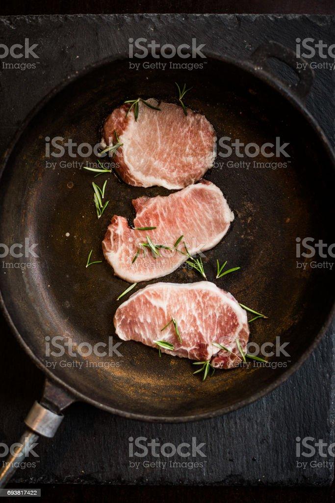 Raw ribeye beef steak with rosemary on pan. Top view. Restaurant stock photo