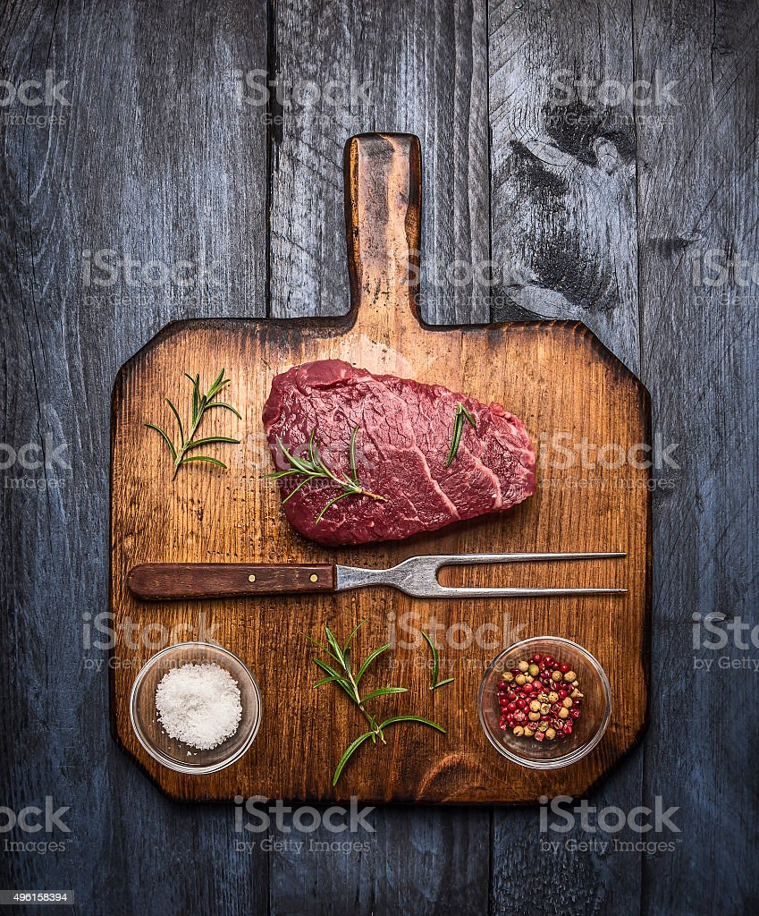 raw ribeye steak  cutting board  rosemary salt pepper stock photo