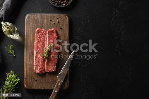808351106 istock photo Raw ribeye steak on cutting board with rosemary on black background. 1251390241