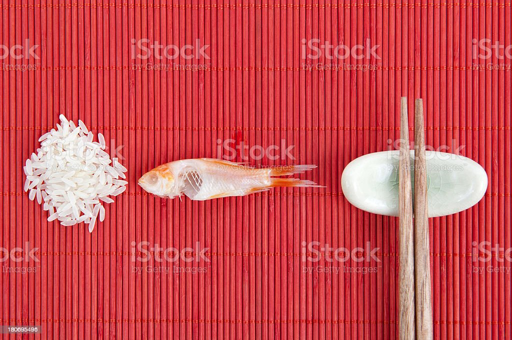 Raw Rice, Eaten Fish And Chopsticks On Place Mat royalty-free stock photo