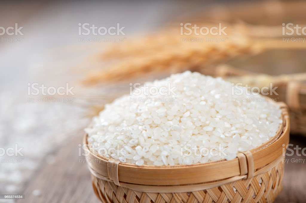 raw rice in a bamboo basket with wheat on wooden background royalty-free stock photo