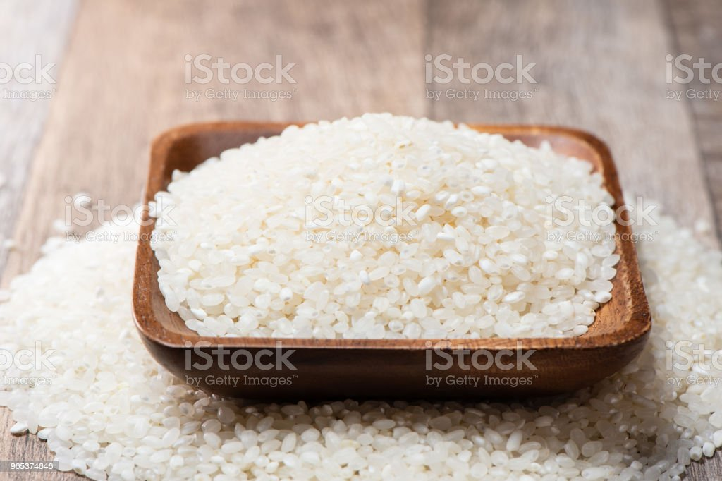 raw rice in a wooden bowl on wooden background zbiór zdjęć royalty-free