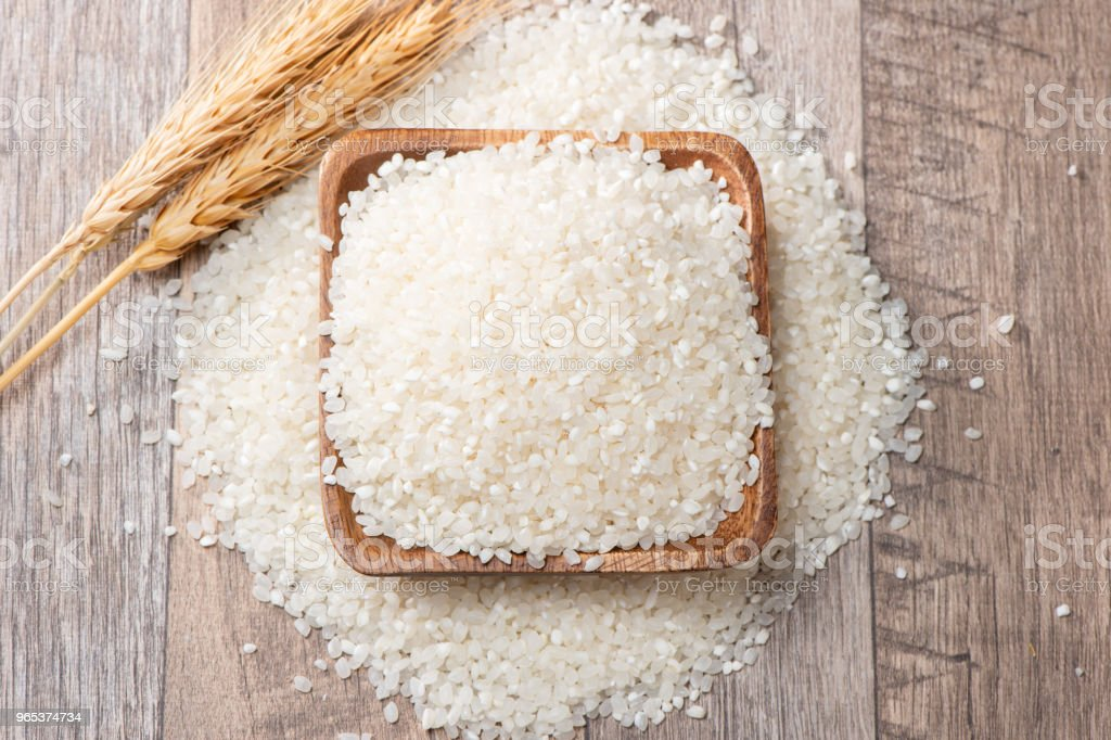 raw rice in a wooden bowl on wooden background royalty-free stock photo