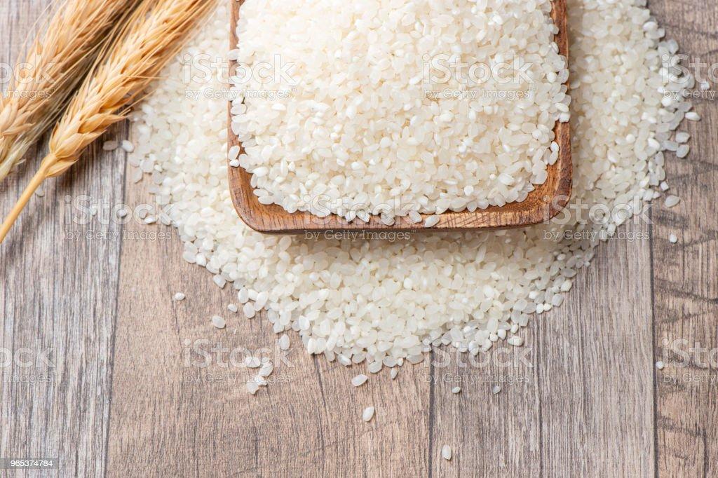 riz cru dans un bol en bois sur fond en bois - Photo de Aliment libre de droits