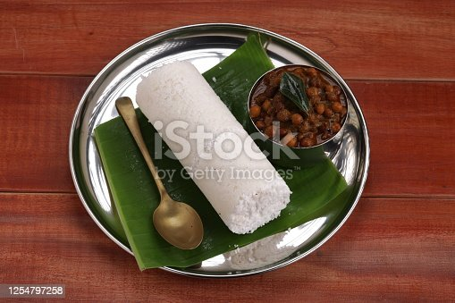 Puttu,raw rice pittu,Arisi maavu puttu with chana curry or Bengal gram cuirry _breakfast items made using raw rice flour, an ideal combination arranged in a steel plate with wooden background