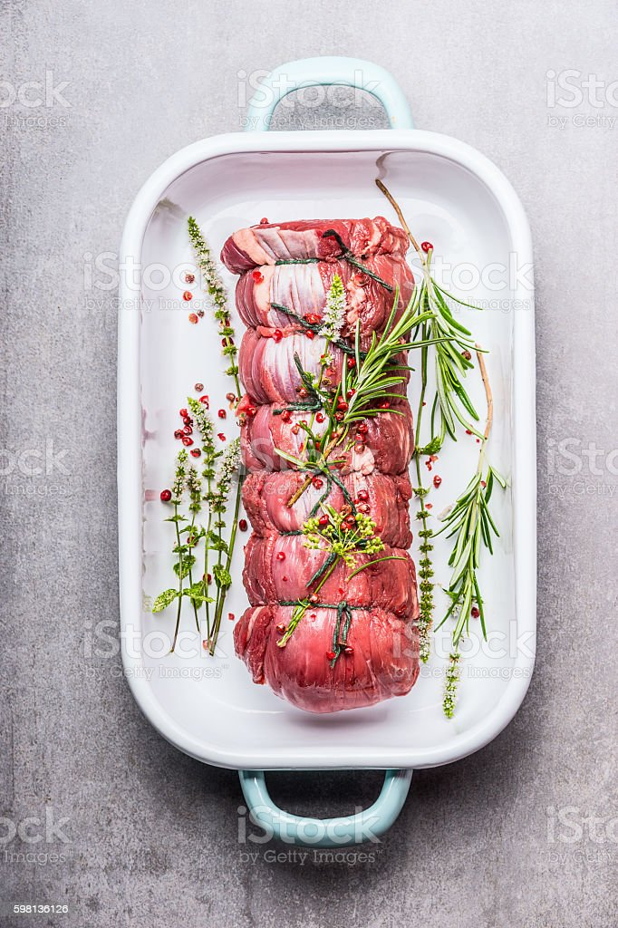 Raw roast beef in a white enamel bowl , top view stock photo