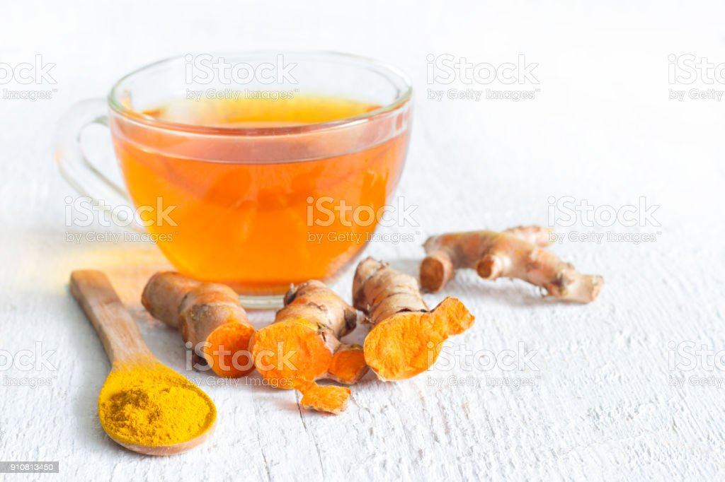 Raw roots of tumeric and tea on white planks detox concept stock photo