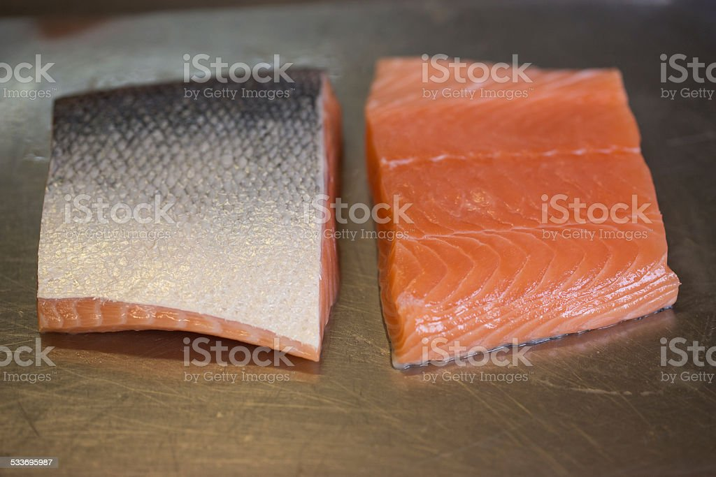 Raw salmon fillets on stainless steel kitchen counter stock photo