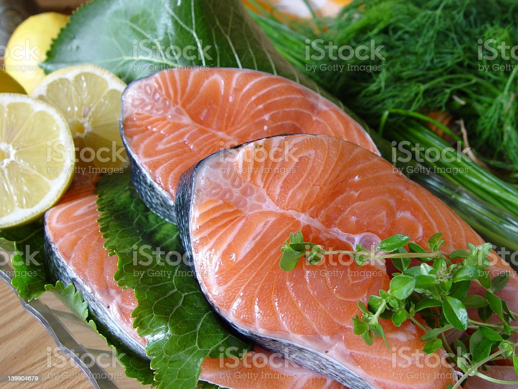 Raw salmon fillets with fresh greens and lemon royalty-free stock photo