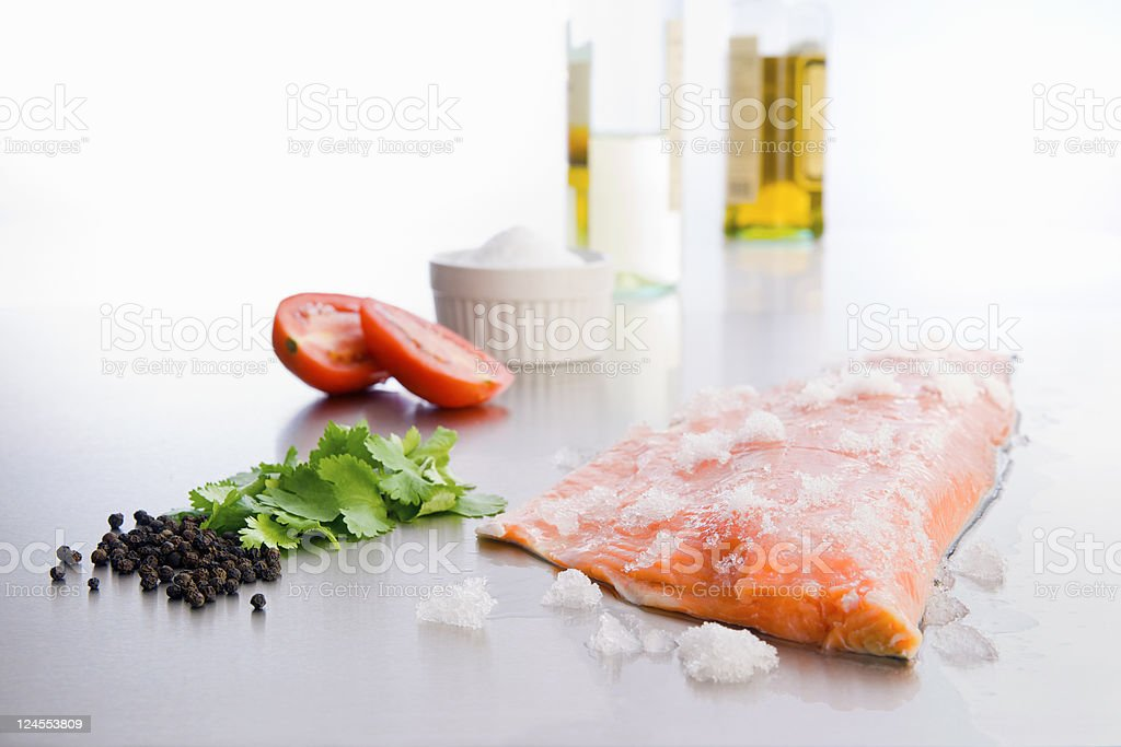 Raw salmon on stainless counter with ingredients royalty-free stock photo