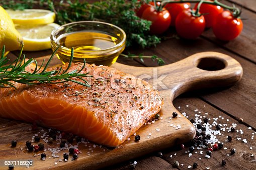 Single raw salmon steak on wooden cutting board. Some ingredients for cooking salmon like lime, salt, pepper, rosemary and olive oil are visible on background. DSRL studio photo taken with Canon EOS 5D Mk II and Canon EF 100mm f/2.8L Macro IS USM