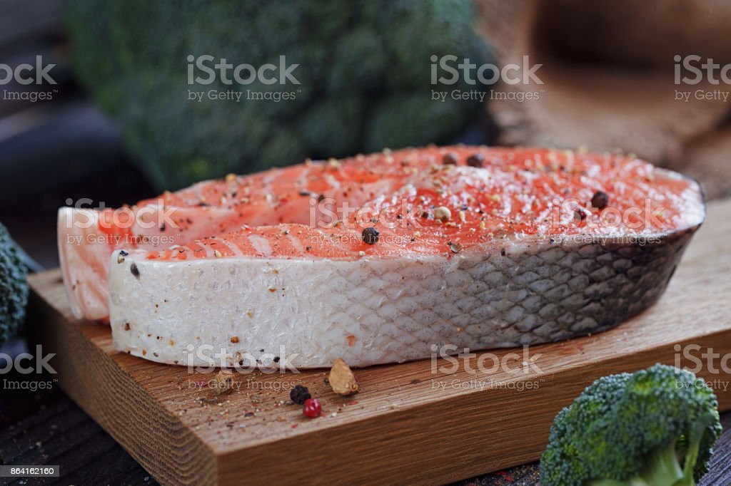 Raw salmon steak with sea salt, pepper and broccoli royalty-free stock photo