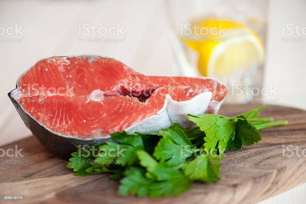 Raw salmon steaks on the wooden board stock photo