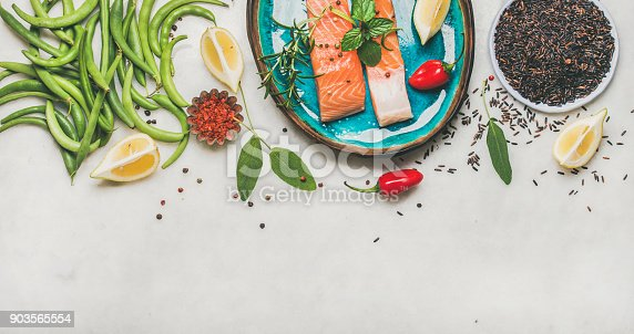 Flat-lay of Raw salmon fish fillet steaks with vegetables, greens, rice, spices and lemon in blue plate over grey marble background, copy space, top view. Clean eating, dieting, power boosting concept