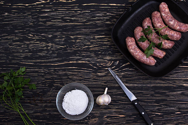 raw sausage in  frying pan with garlic on wooden background stock photo
