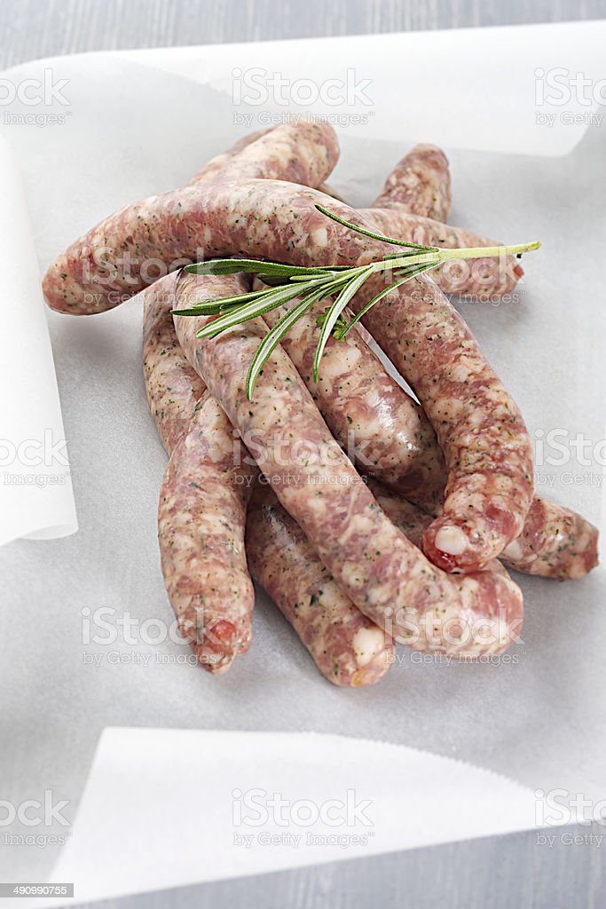 Raw sausages chipolata with herbs stock photo
