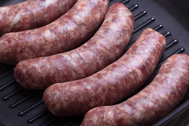 raw sausages on a  pan stock photo
