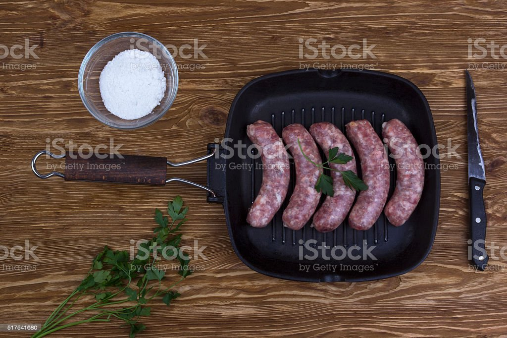 raw sausages on a  pan, salt and knife, wooden background stock photo