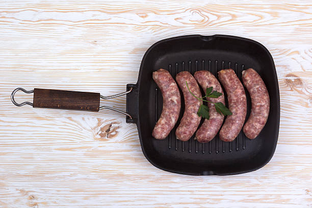 raw sausages on a  pan,  wooden background stock photo