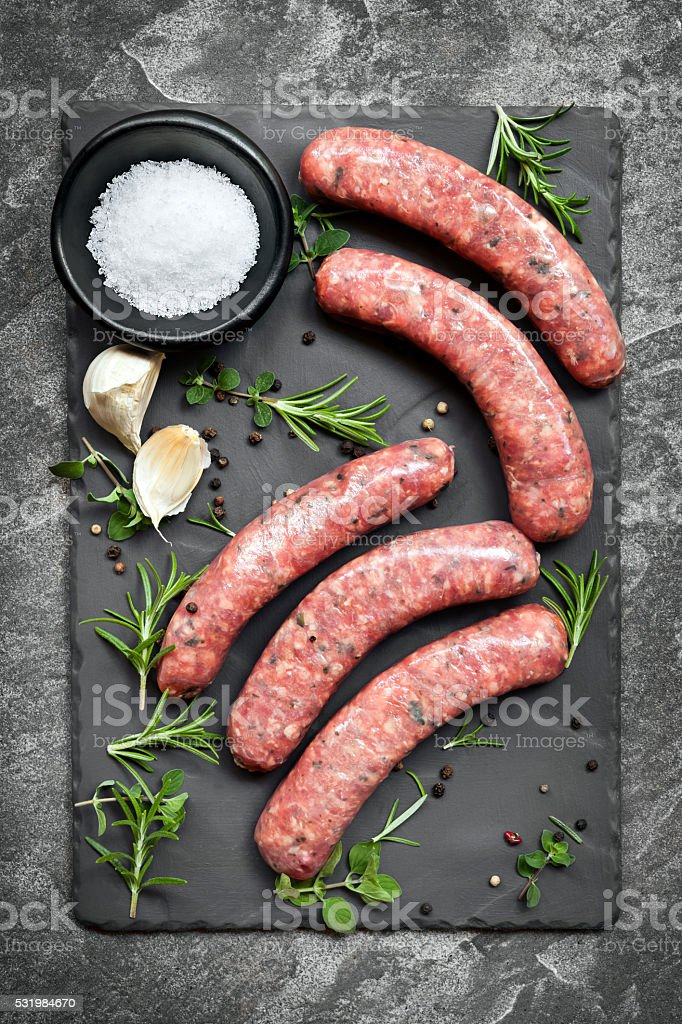 Raw Sausages on Slate Overhead View stock photo