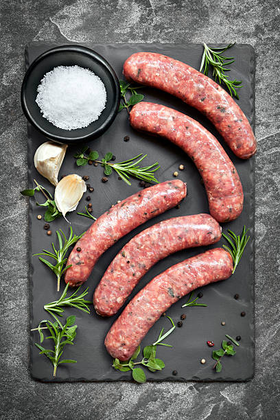 raw sausages on slate overhead view - sausage stock photos and pictures