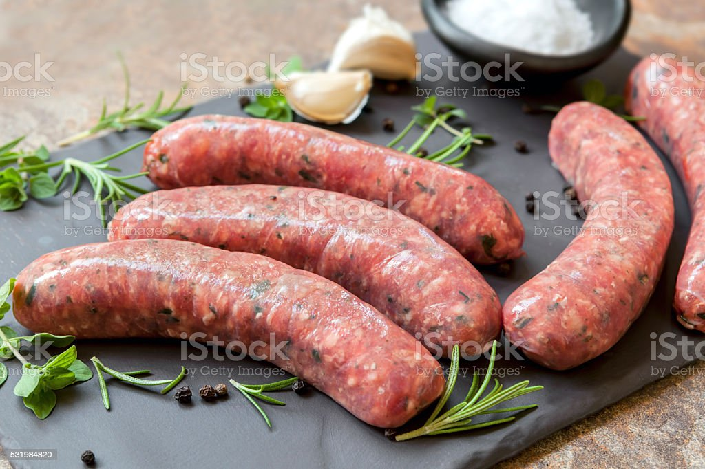 Raw Sausages on Slate with Herbs and  Spices stock photo