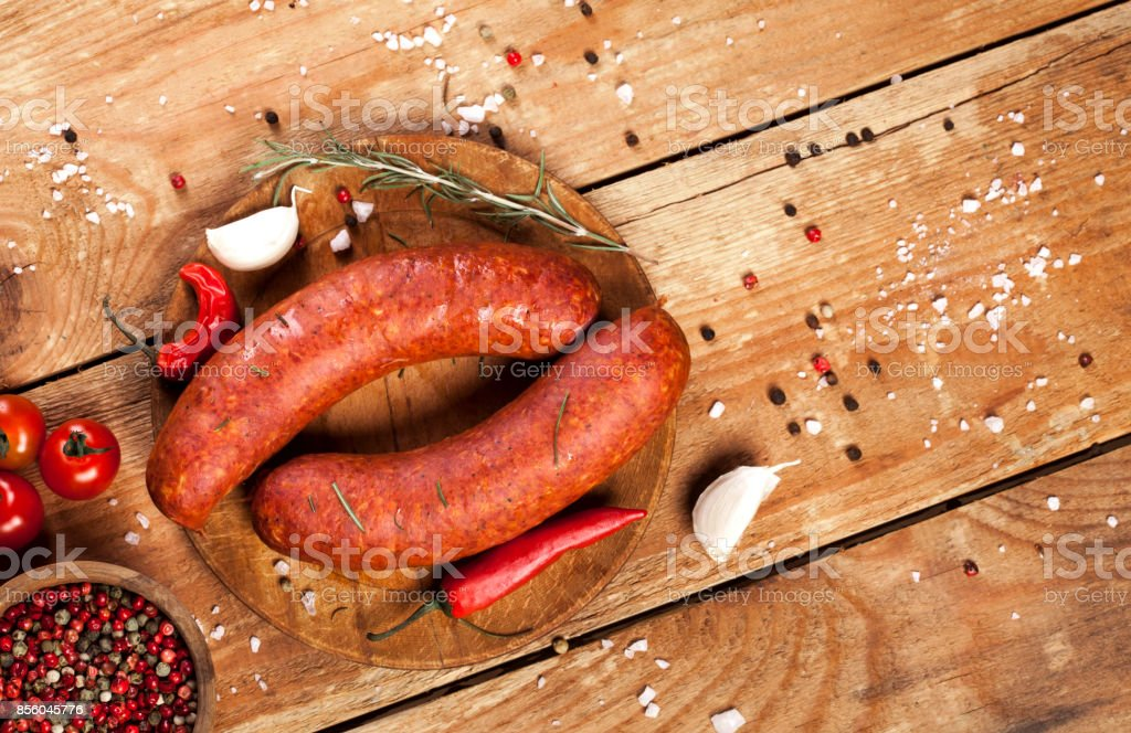 Raw sausages on wooden background stock photo