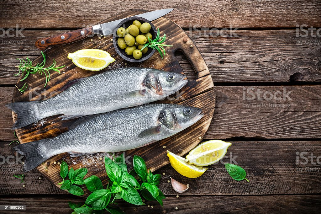 raw sea bass fish on wooden background top view stock photo
