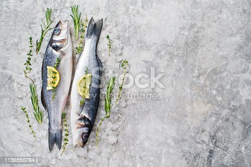 496065234istockphoto Raw sea bass on ice with rosemary, thyme and lemon. Gray background, top view, space for text. 1136550764