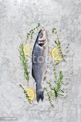 496065234istockphoto Raw sea bass on ice with rosemary, thyme and lemon. Gray background, top view, space for text. 1136551947