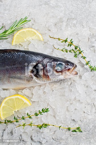 496065234istockphoto Raw sea bass on ice with rosemary, thyme and lemon. Gray background, top view. 1136552071