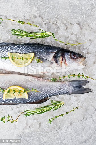 496065234istockphoto Raw sea bass on ice with rosemary, thyme and lemon. Gray background, top view. 1136552289