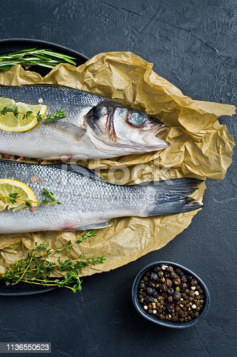496065234istockphoto Raw sea bass on Kraft paper with rosemary, thyme and lemon. Black background, top view. 1136550523