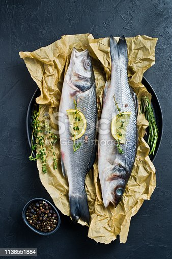 496065234istockphoto Raw sea bass on Kraft paper with rosemary, thyme and lemon. Black background, top view. 1136551884