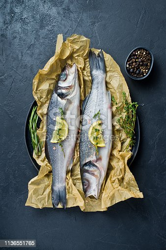496065234istockphoto Raw sea bass with rosemary, thyme and lemon. Black background, top view. 1136551765