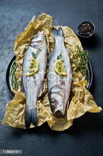 496065234istockphoto Raw sea bass with rosemary, thyme and lemon. Black background, top view. 1136551911