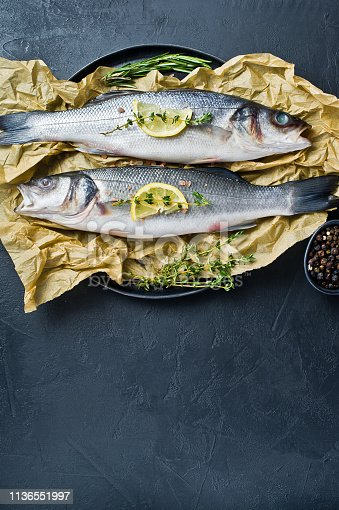496065234istockphoto Raw sea bass with rosemary, thyme and lemon. Black background, top view, space for text. 1136551997