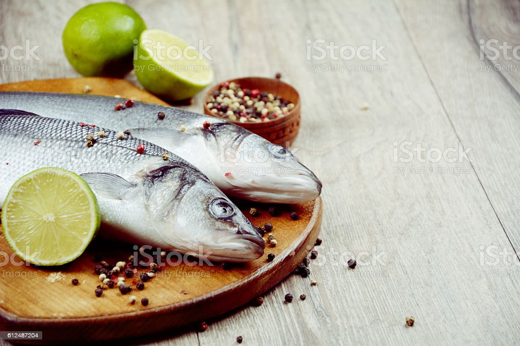 Raw seabass fish on the wooden board stock photo