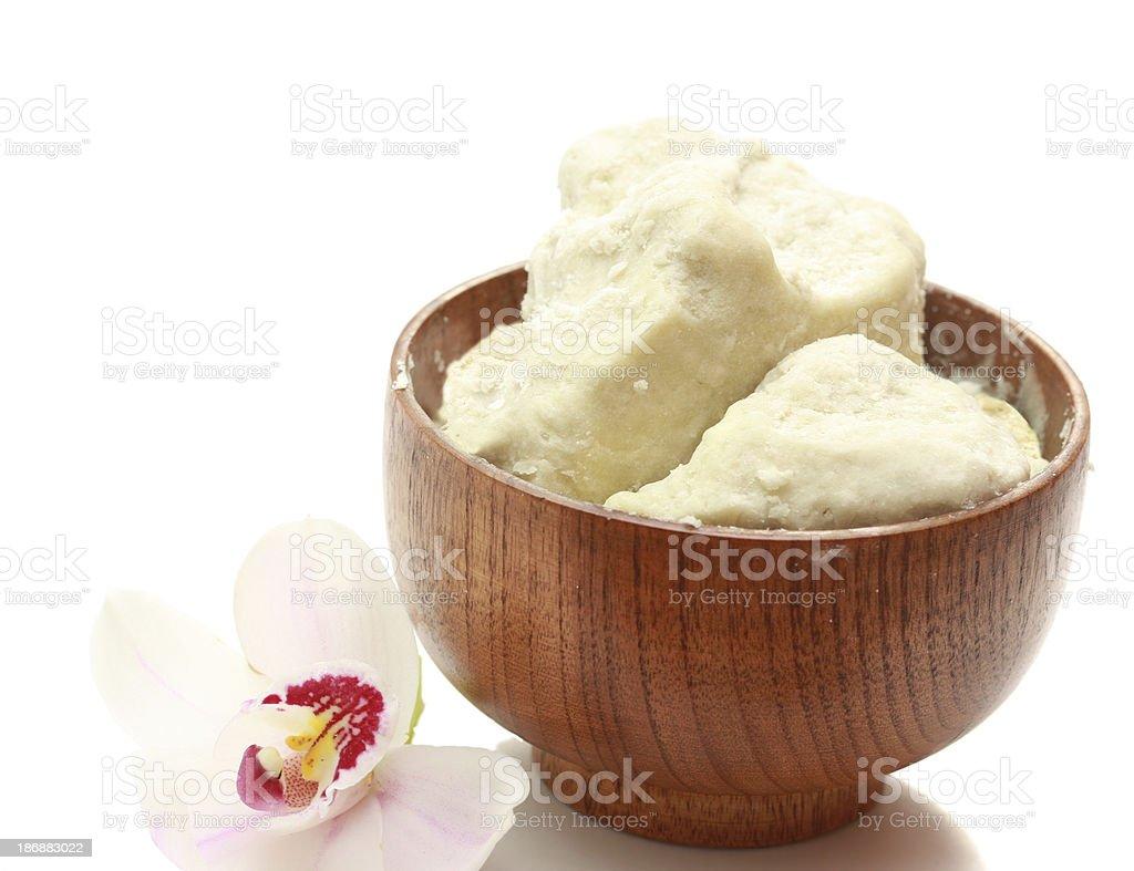 Raw du beurre de karité dans un bol en bois avec orchidée - Photo