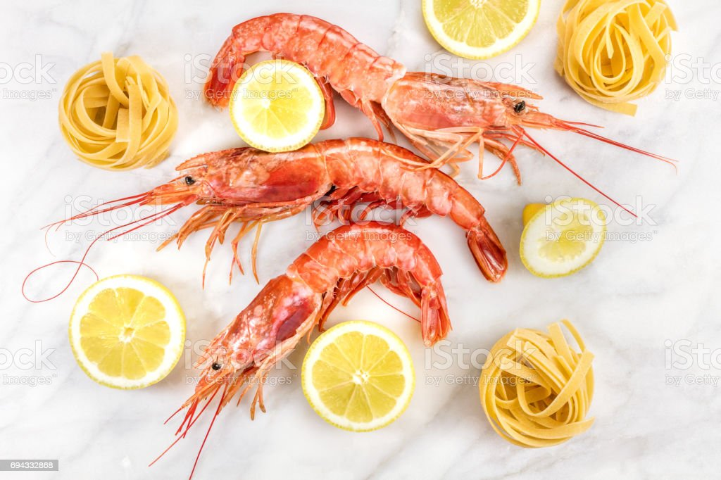 Raw shrimps with lemon and pasta on marble table stock photo