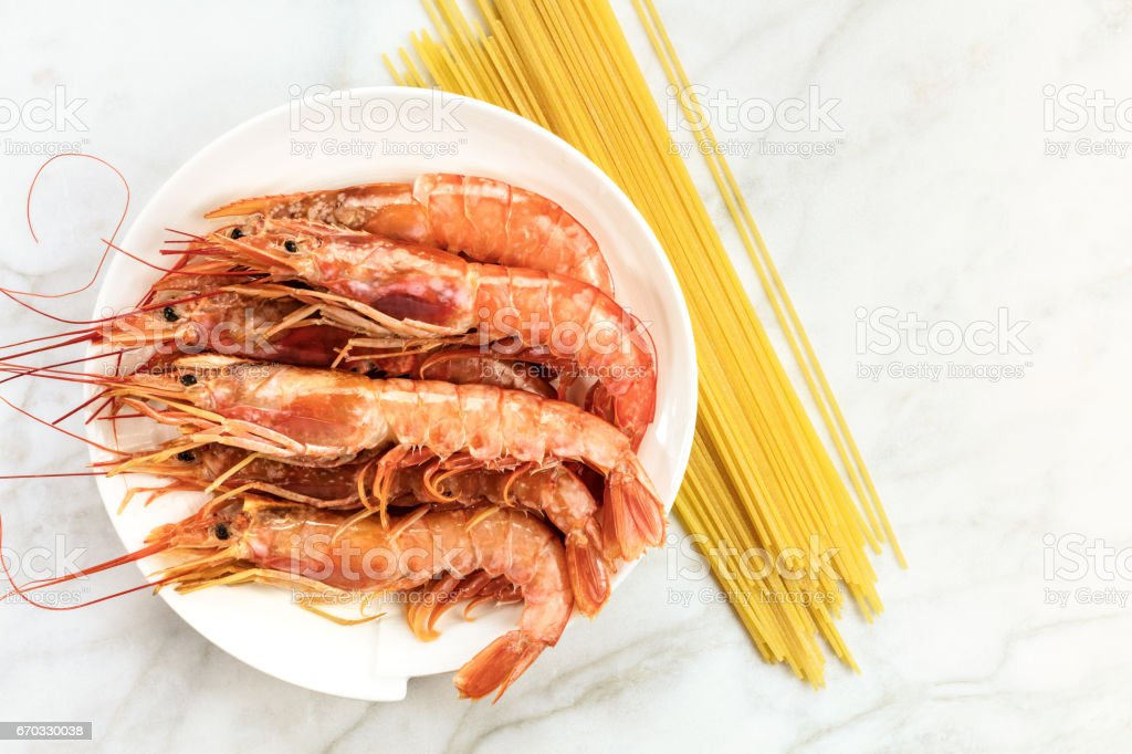 Raw shrimps with pasta, and copyspace on white table stock photo