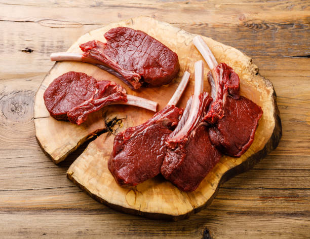 Raw sliced Venison Ribs on wooden background stock photo