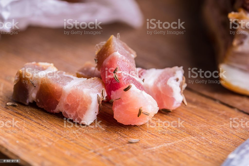 Raw smoked bacon slices on wooden board with cumin. stock photo