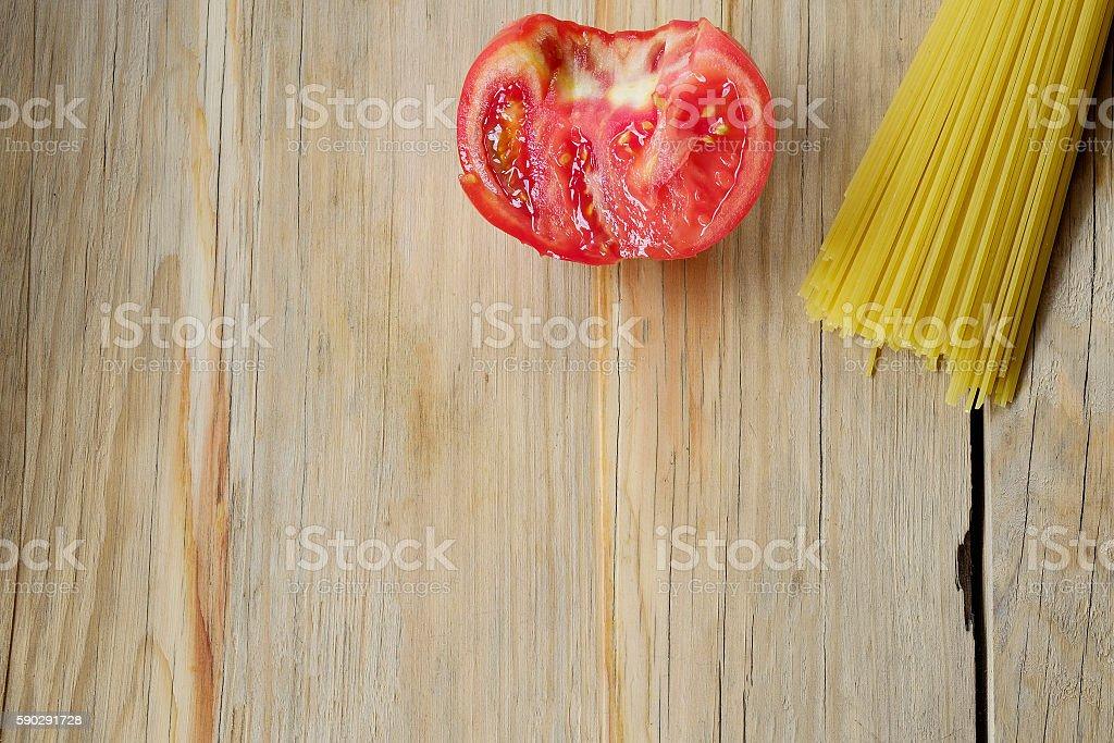 Raw spaghetti pasta and half tomato on wood background royaltyfri bildbanksbilder